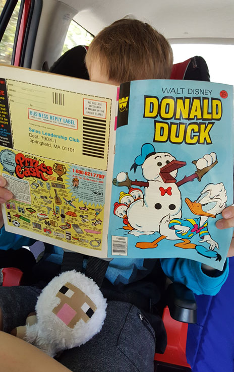 Reading a Donald Duck comic book in the car.