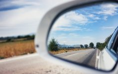 Car side mirror reflects road.