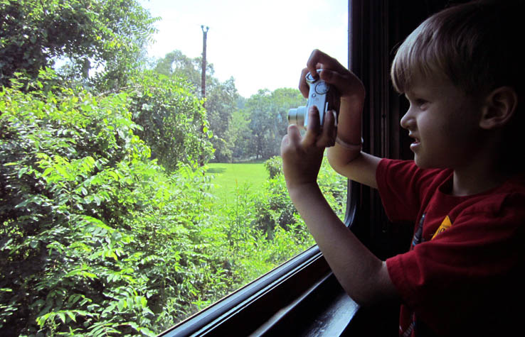 Child taking photo with digital camera out window of train.