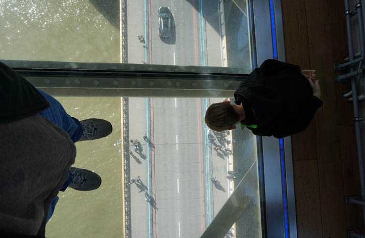 Boy looking at cars through glass floor, Tower Bridge, London