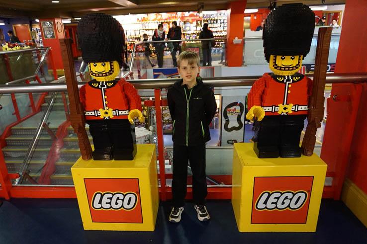 Boy posing between LEGO brick British guards in Hamley's Toy Shop, London