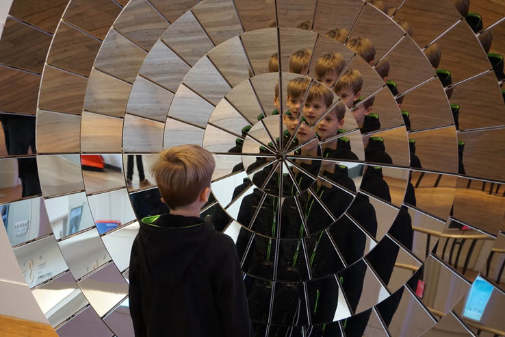 Boy looks in mirror at Science Museum, London
