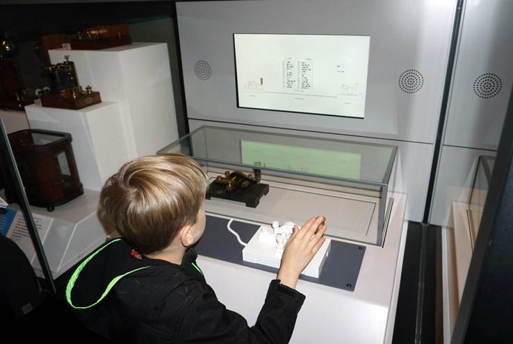 Boy practices Morse code on telegraph, Science Museum, London