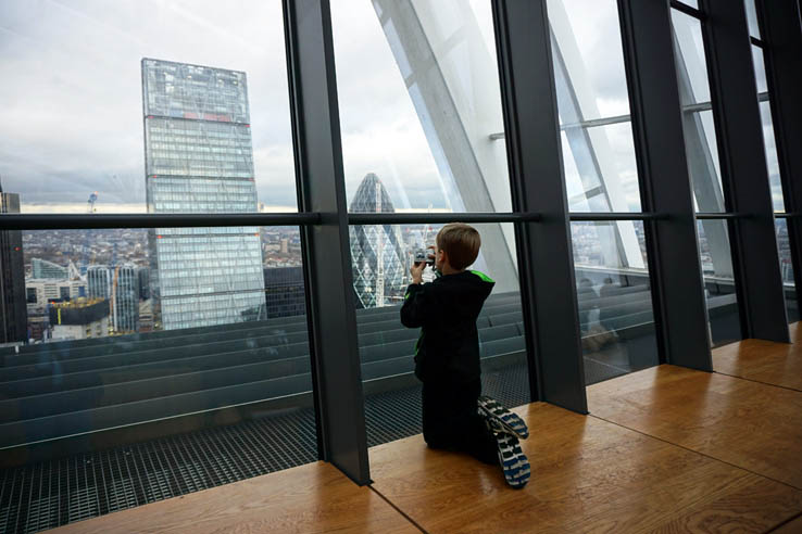 Boy taking photo of skyscrapers, view from Sky Garden in 20 Fenchurch Street, London