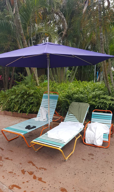 Chairs with umbrella for shade at Aquatica Orlando water park.