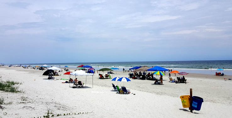People on the beach and beach umbrellas and ocean waves at Ponce Inlet Florida