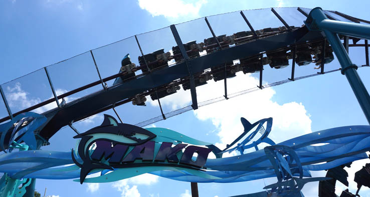 Mako roller coaster sign with coaster car going by overhead at SeaWorld Orlando